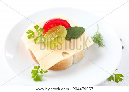 Cheese sandwich with tomato, grape and parsley.
