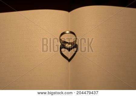 A Heart Made From The Shadow Of A Ring On A Blank Book With Lines