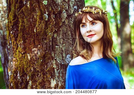 Young woman with a wreath on her head leaning against a tree trunk