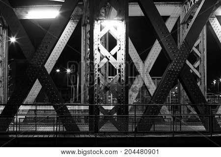 Metal Construction Of A Bridge In The City Of Dieppe, Normandy, France. Night Urban Scene With City