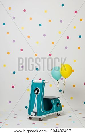 homemade turquoise children's toy motorcycle with balloons on a white background