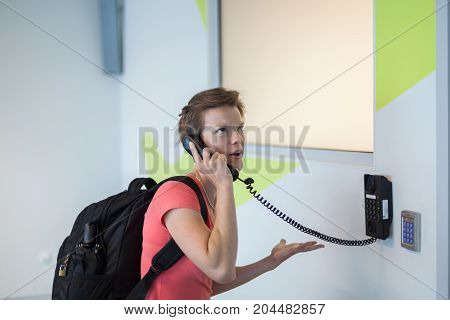 The Young Woman Has Been Complaining To The Airport By Telephone