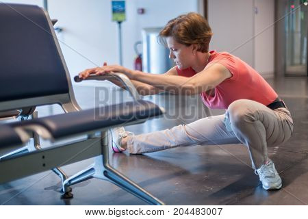 Young Woman Doing Exercises In The Airport Hall While Waiting For The Plane
