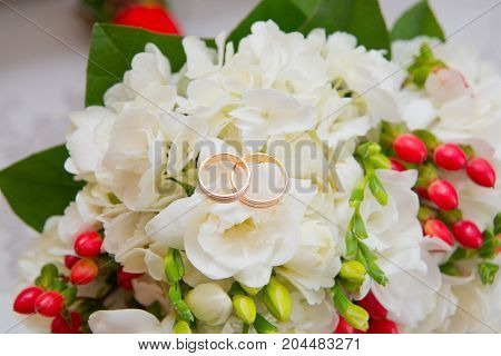 Two Gold Wedding Rings Lie On A Bouquet With White Flowers And Red Berries.