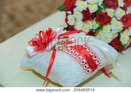Two Gold Wedding Rings Lie And A Bouquet Of Red Roses.