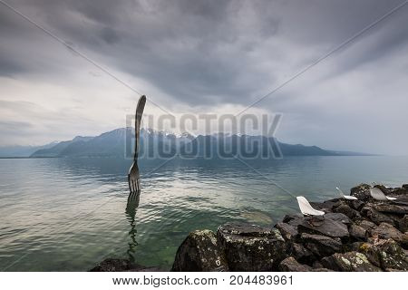 Vevey Switzerland - May 25 2016: Giant steel fork in water of Geneva lake in cloudy weather Vevey Switzerland.The fork went up in 1995 to mark the 10th anniversary of the Alimentarium Veveys Food Museum.