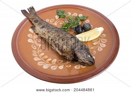 Baked carp on a clay plate with lemon, parsley and olives. Isolated on a white background.
