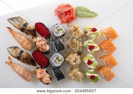 Delicious sushi rolls set with wasabi and marinated ginger. On a table as a background.