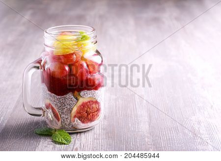 Chia seed yogurt and fruit (fig and grapes) layered healthy snack in a jar