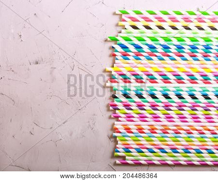 Colored striped drink straws over cement grunge surface