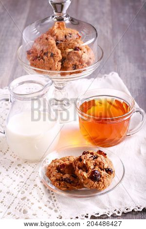 Oat cookies with cranberry dried apricot and nuts on saucer and cup of tea