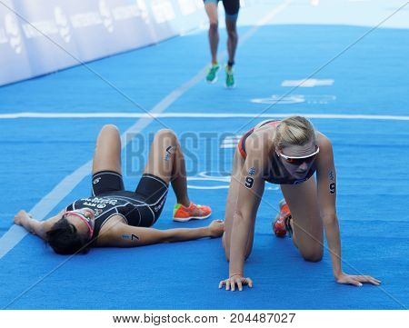 STOCKHOLM - AUG 26 2017: Exhausted triathletes Takahashi and Kasper and Brown after the finish in the Women's ITU World Triathlon series event August 26 2017 in Stockholm Sweden