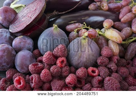 Purple food. Background of berries fruits and vegetables. Fresh figs plums raspberries beet eggplant and grapes. Top view