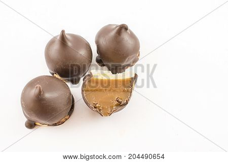Cones stuffed with sweet or caramel and bathed in whole chocolate and one cut in half. White background.