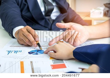 Business people listen to the analysis of the company employees,Executives and employees are analyzing the work,Executives point pen in hand to chart.