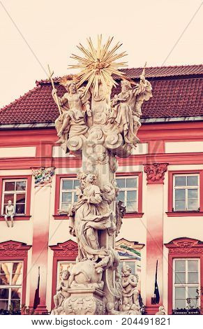 Holy trinity column and Goose on a string theatre building Brno Moravia Czech republic. Baroque architecture. Symbolic object. Red photo filter.