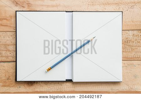 Top view close up of open notebook and blue pencil with white blank space use for your texts display