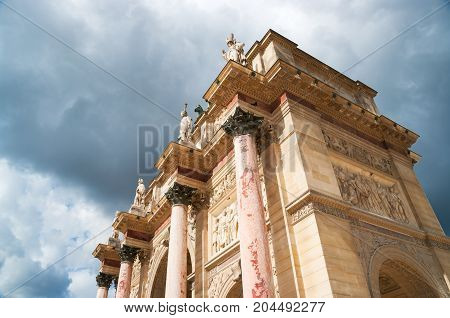 Top of the triumphal arch of the Carrousel against cloudy sky in Paris