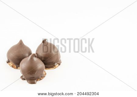 Three cones of dulce de leche or syrup bathed in dark chocolate. Cake shop. White background.
