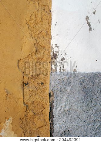 old rough painted wall with peeling concrete decay with grey white and orange areas