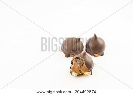 Three cones of dulce de leche bathed in chocolate and one bitten. White background.