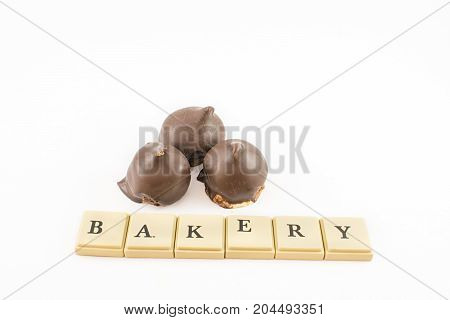 ''bakery'' written with chips and cones of dulce de leche and chocolate around. White background.
