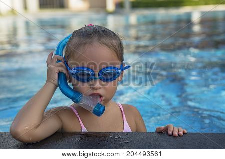 A happy young girl relaxing on the side of a swimming pool wearing goggles and snorkel