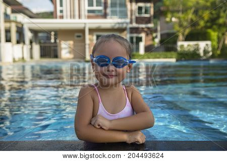 A happy young girl relaxing on the side of a swimming pool wearing goggles