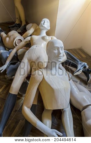 A bunch of mannequins lying on the parquet under the sun from the window
