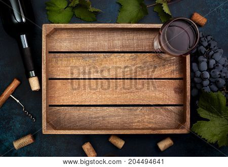wooden box with a glass of wine a bottle of wine on a blue background. view from above