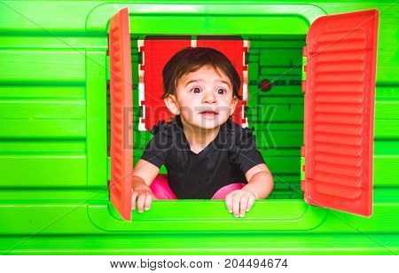 baby inside toy house playhouse child look out the window