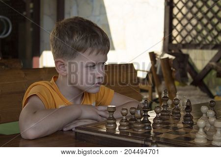 Boy playing chess in summer house. Little clever boy concentrated and thinking while playing chess outdoor. is going to make a move in chess. concept of logics and intellection, education.