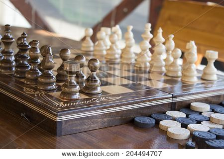 Chess on the game board. Checkers on the table near the game board outdoor. concept of  intellection. wooden table and bench with chess on the summer house.