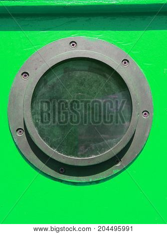 close up of rusty distressed porthole on a green wooden boat with screws in summer light