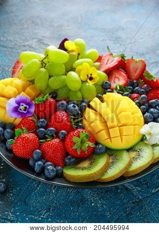 Colorful Mixed Fruit platter with Mango, Strawberry, Blueberry, Kiwi and Green Grape. Healthy food.