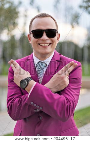 joke portrait of a young businessman in pink suit joking shows pistols with fingers