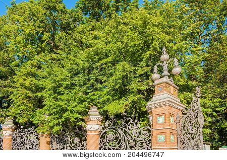 St. Petersburg Russia. Fence of the Michaels Garden in St Petersburg Russia in sunny summer day. Architecture view of St Petersburg landmark framed by park green trees