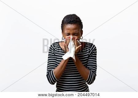 Young African woman blowing her nose on a tissue conceptual of seasonal flu rhinitis or a respiratory allergy like hayfever isolated on white