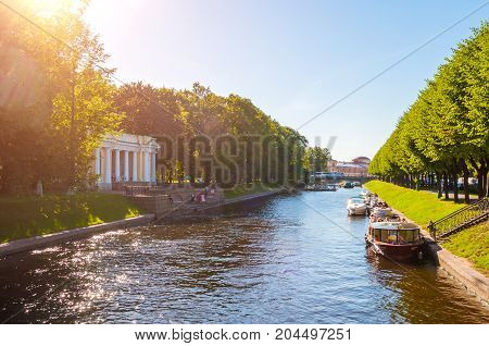 ST PETERSBURG RUSSIA - AUGUST 15 2017. Rossi Pavilion in the Michael Garden and the Moika river with pleasure boats in St Petersburg Russia