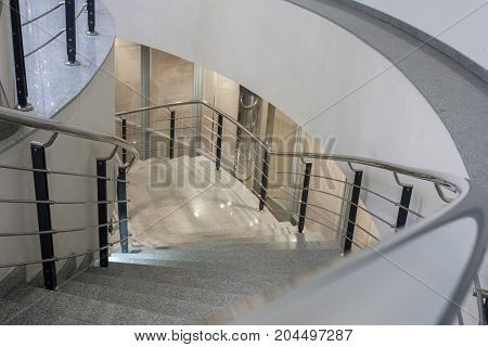 Perspective view down to lit stone spiral staircase with metal railing.