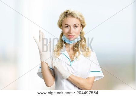 Young nurse putting on gloves. Beautiful blond lady medic with face mask putting on white sterilized gloves.
