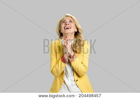 Happy grateful young blond woman. Joyful young lady showing her gratitude clasping her hands and lifts eyes to thew sky over grey background.