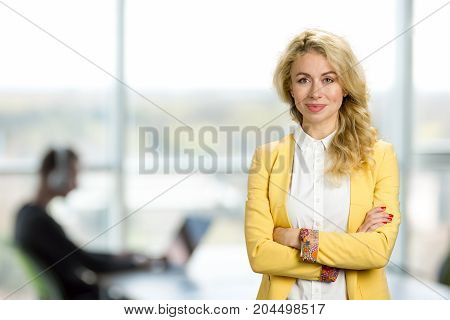 Beautiful business lady crossed arms. Attractive young european woman crossed her arms on office window background.