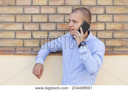 He Leaned Against The Wall And Spoke Over The Cell Phone
