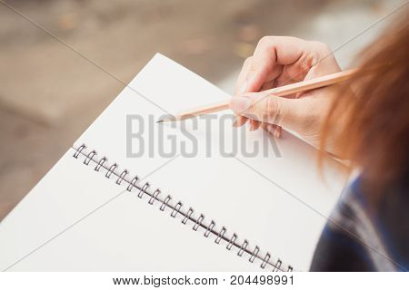Close up of woman's hands writing in spiral notepad placed on wooden desktop with various items. Vintage effect style pictures.