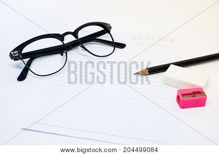 Black glasses white paper pencil pink sharpener and eraser (rubber) for write your note - concept relax.