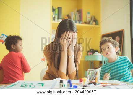 Asian teacher kindergarten hands closed both ears of her in an upset of failed to quell quited naughty of the boys in class at preschool kids argument. Vintage effect style pictures.