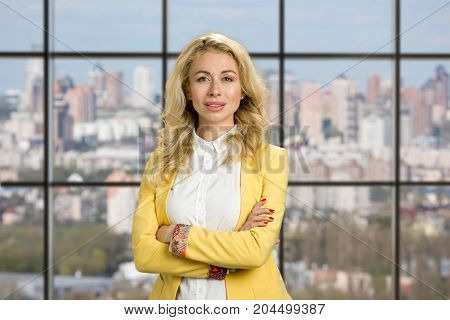 Beautiful young woman with crossed arms. Portrait of cheerful young business lady standing with crossed arms against office window background, front view.