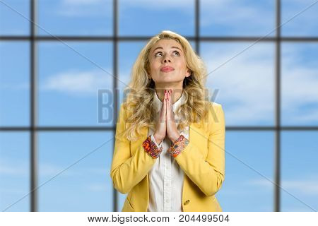 Beautiful young business woman praying. Attractive young office worker praying and looking on heaven standing on blue sky office window background.