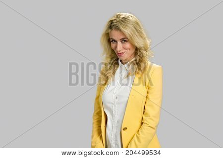 Portrait of positive young woman. Attractive blonde lady in yellow jacket looking embarrassed standing on grey background close up.